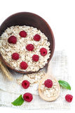 Oatmeal flakes and raspberries on white background. Oatmeal flakes and raspberries isolated on white background Royalty Free Stock Photo