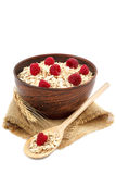 Oatmeal flakes and raspberries on white background. Oatmeal flakes and raspberries isolated on white background Royalty Free Stock Photography