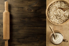 Oatmeal flakes in a wooden bowl with a spoon, ears of wheat, pot of flour, kitchen utensils on the table. Royalty Free Stock Images