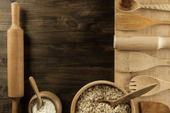 Oatmeal flakes in a wooden bowl with a spoon, ears of wheat, pot of flour, kitchen utensils on the table. Stock Photo