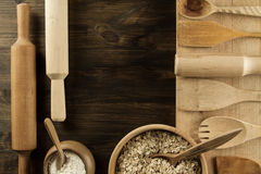 Oatmeal flakes in a wooden bowl with a spoon, ears of wheat, pot of flour, kitchen utensils on the table. Stock Photos