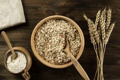 Oatmeal flakes in a wooden bowl with a spoon, ears of wheat, pot of flour on the table. Stock Image