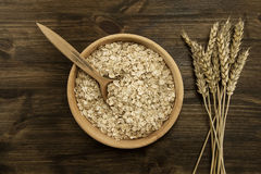 Oatmeal flakes in a wooden bowl with a spoon, ears of wheat on the table. Stock Photo