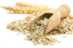 Oatmeal flakes with wooden scoop Royalty Free Stock Photo