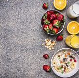 Oatmeal with fruit and freshly squeezed orange juice border ,place for text  wooden rustic background top view close up Stock Photo