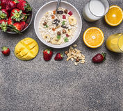 Oatmeal with fruit and freshly squeezed orange juice border ,place for text  wooden rustic background top view close up Royalty Free Stock Photo