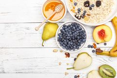 Oatmeal with fruit and honey on a white wooden table. Healthy food. Top view royalty free stock image