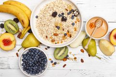 Oatmeal with fruit and honey on a white wooden table. Healthy food. Top view royalty free stock images