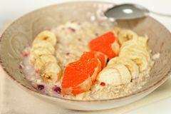 Oatmeal with fruit in nice bowl. Oatmeal with fruit in nice rustic bowl Royalty Free Stock Image