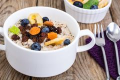 Oatmeal with fruit and nuts-hearty and tasty breakfast Royalty Free Stock Photography