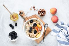 Oatmeal with fruits, nuts and honey stock images