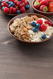 Oatmeal, granola, nuts and berries in bowls on wooden background Stock Photography