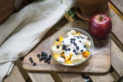 Oatmeal or granola with yogurt and fruits and berries. Peach, mango, banana, blueberry, raspberry apple stock images