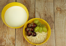 Oatmeal with grapes and milk on a wooden countertop Stock Images