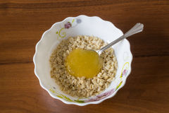 Oatmeal with honey. Healthy and nutritious food on dark wood background Stock Image