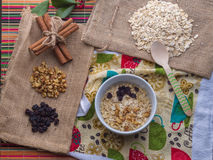Oatmeal with ingredients. Oatmeal in milk with ingredients of raisin, walnut, cinnamon sticks Stock Images