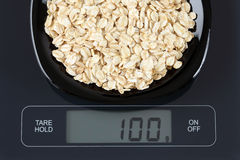 Oatmeal on kitchen scale. Oatmeal in a black plate on digital scale displaying 100 gram Stock Image