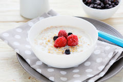 Oatmeal with milk and berries Stock Image
