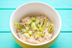 Oatmeal with milk and kiwi in a yellow bowl Royalty Free Stock Photo