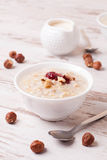 Oatmeal with milk, nuts and strawberry jam and milk jug Stock Photos