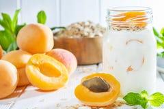 Oatmeal milkshake, smoothie or yogurt with fresh apricot on a white wooden background stock image