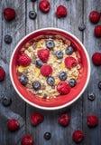 Oatmeal muesli με τα φρέσκα μούρα στο κόκκινο κύπελλο στο μπλε αγροτικό backgrund, τοπ άποψη Έννοια τροφίμων αθλητισμού, υγείας κ Στοκ φωτογραφία με δικαίωμα ελεύθερης χρήσης