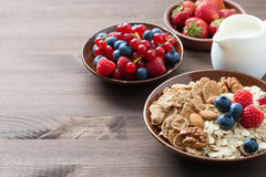 Oatmeal and muesli in a bowl, berries and milk. Oatmeal and muesli in a bowl, fresh berries and milk on wooden background (with space for text), horizontal Stock Photography