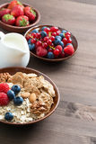 Oatmeal and muesli in a bowl, fresh berries and jug of milk. On wooden table, vertical Royalty Free Stock Images
