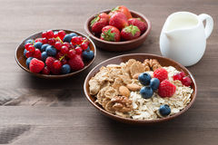 Oatmeal and muesli in a bowl, fresh berries and milk on wood Royalty Free Stock Images
