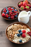 Oatmeal and muesli in a bowl, fresh berries and milk Stock Photo