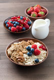 Oatmeal and muesli in a bowl, fresh berries and milk. On wooden table, vertical, top view Stock Photos
