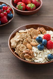 Oatmeal and muesli in a bowl, fresh berries on wooden background. Vertical, close-up Royalty Free Stock Photos