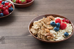 Oatmeal and muesli in a bowl, fresh berries on wooden table Stock Images
