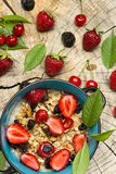 Healthy Breakfast. Oatmeal with muesli and fruit fresh strawberries, cherries and prunes with honey on the cut surface of wood. Oatmeal with muesli and fruit Royalty Free Stock Photos