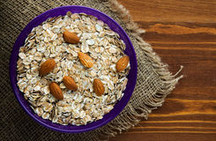 Oatmeal with nuts   almonds . Oatmeal  on a wooden background Royalty Free Stock Photo