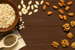 Oatmeal with nuts in bowl on brown background stock image
