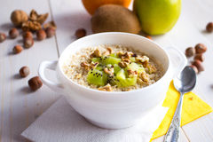 Oatmeal with nuts and fruits for breakfast. In a white bowl stock photography
