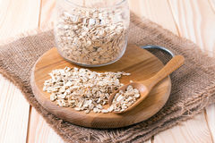 Oatmeal or oat flakes in bowl and scoop on dark wooden table. On the table Royalty Free Stock Photography