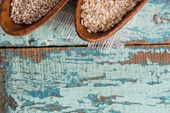 Oatmeal or oat flakes on dark wooden table. In a wooden plate. Grain of cereals. Healthy eating. On a textured old blue green background Stock Photography