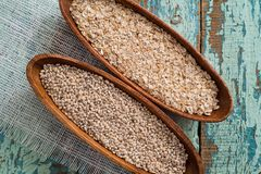 Oatmeal or oat flakes on dark wooden table. In a wooden plate. Grain of cereals. Healthy eating. On a textured old blue green background Royalty Free Stock Images