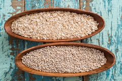 Oatmeal or oat flakes on dark wooden table. In a wooden plate. Grain of cereals. Healthy eating. On a textured old blue green background Stock Photos