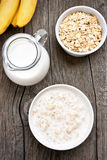Oatmeal, oats in bowl and jug of mik Stock Photo
