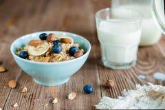 Oatmeal owsianki śniadanie z dokrętkami, jagodami i mlekiem, Zdjęcie Stock
