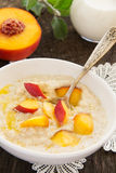 Oatmeal with peaches. Royalty Free Stock Image