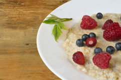 Oatmeal in plate on wooden background Royalty Free Stock Photo