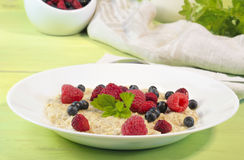 Oatmeal in plate on wooden background Royalty Free Stock Photos