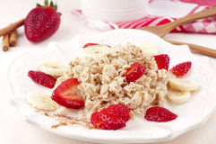 Oatmeal porridge. With milk, strawberry, banana and cinnamon Stock Image