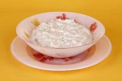 Oatmeal Porridge. Ready oatmeal porridge on a yellow background Stock Photos