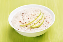 Oatmeal porridge with apple slices and cinnamon Stock Image
