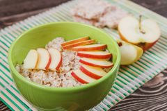 Oatmeal Porridge with Apple Slices in Green Bowl Stock Photo
